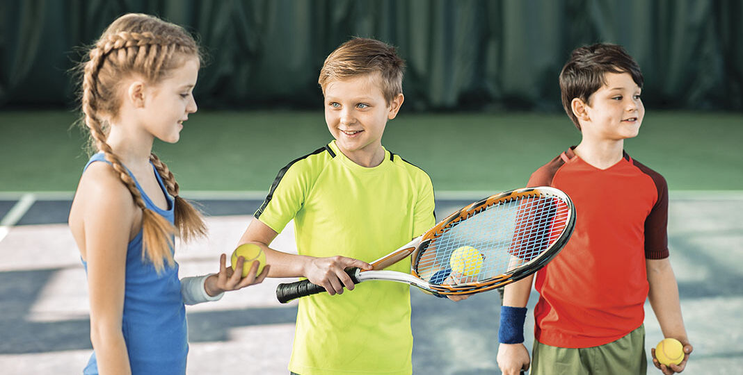 Happy children playing tennis on playground