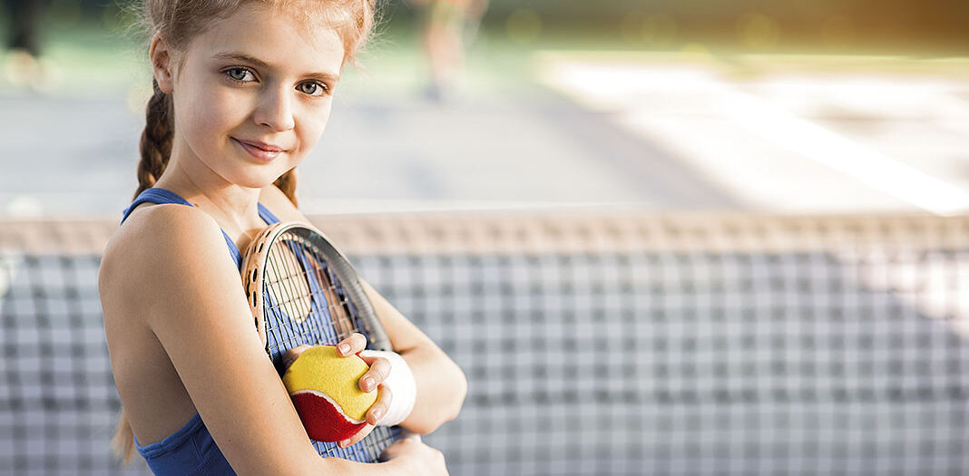 Cheerful female kid playing tennis with enjoyment